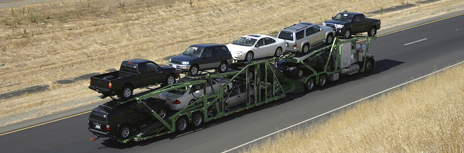 Open auto transport carrier hauling vehicles from Alabama to California
